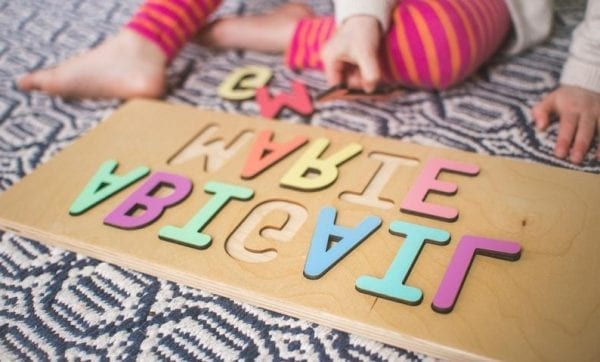 """A child placing a letter in a puzzle for the name """"Abigail Marie"""""""