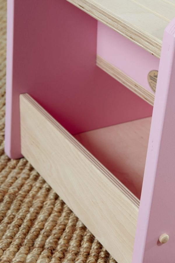 a close-up on the back and inside of a wooden step stool for kids with pink sides