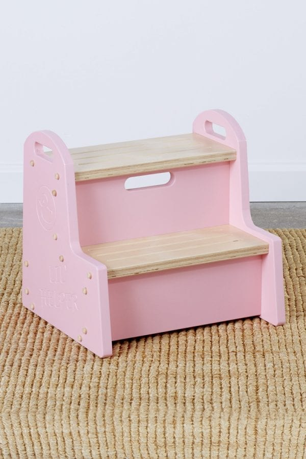 """a wooden step stool for kids with pink sides bearing a duck logo above the words """"Lil Helper"""""""