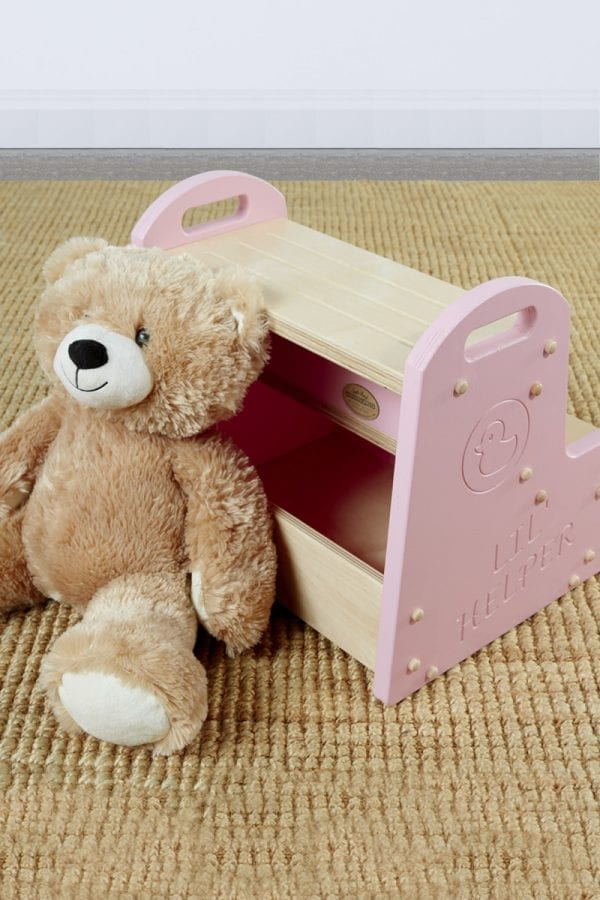 """a teddy bear leans against a wooden step stool for kids with pink sides bearing a duck logo above the words """"Lil Helper"""""""