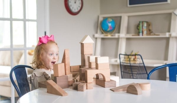 a young girl with a pink hair bowgasps excitedly at an assembled castle-like building made from the set of wood blocks