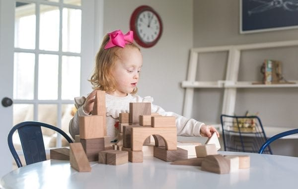 a young girl with a pink hair bow stares thoughtfully as she places a block while creating a structure